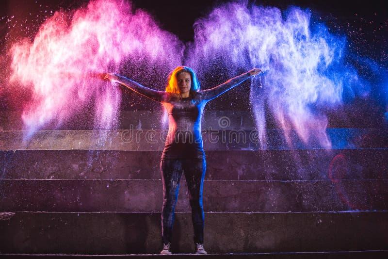 Lyckliga kvinnakast färgar pulver i form av ängelvingar royaltyfri foto