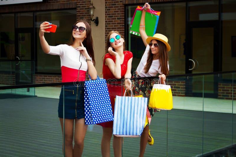 Lyckliga kvinnavänkunder med shoppingpåsar som gör selfie royaltyfri fotografi