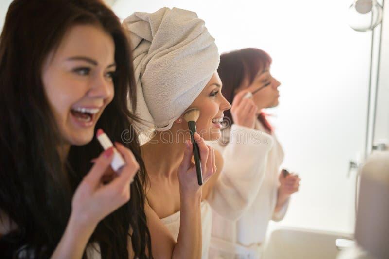 Lyckliga kvinnavänner som gör smink i badrum royaltyfri fotografi
