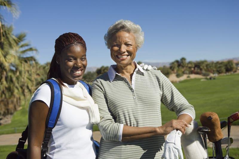 Lyckliga kvinnliga golfare på golfbanan royaltyfri bild
