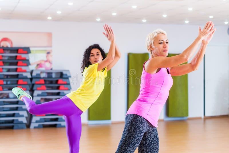 Lyckliga kvinnliga idrottsman nen som gör aerobics, övar eller den Zumba dansgenomköraren för att förlora vikt under gruppgrupper royaltyfri bild