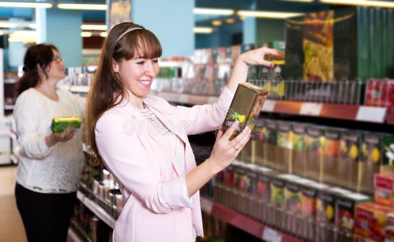 Lyckliga kvinnliga kunder som väljer svart te arkivfoton