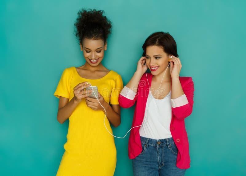 Lyckliga kvinnliga vänner lyssnar till musik på studiobakgrund royaltyfri fotografi