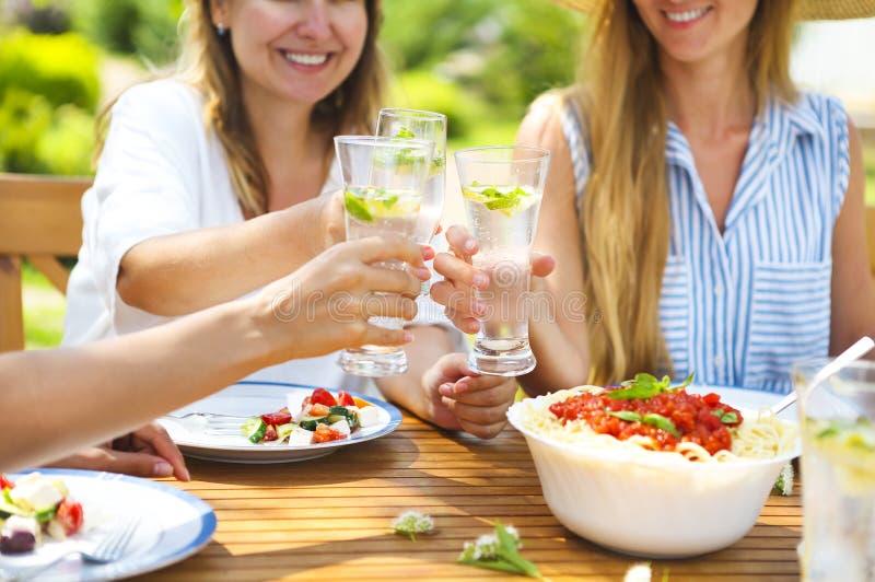 Lyckliga kvinnliga vänner med exponeringsglas av lemonad på att äta middag tabellen in royaltyfria bilder