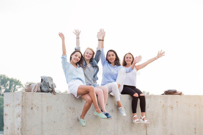 Lyckliga kvinnliga vänner som har gyckel på helg, på picknick utomhus Unga le studentflickor som sitter på den konkreta gränsen royaltyfri bild