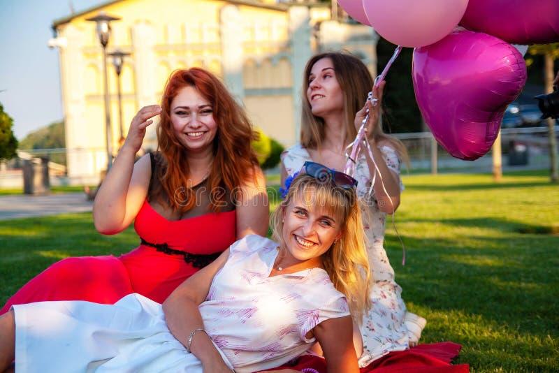 Lyckliga kvinnliga vänner som spelar och har gyckel i grönt gräs arkivbilder