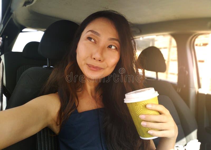 Lyckliga kvinnliga vänner som spelar och har gyckel i grönt gräs Stående av en härlig asiatisk kvinna som sitter i en bil och le arkivfoton