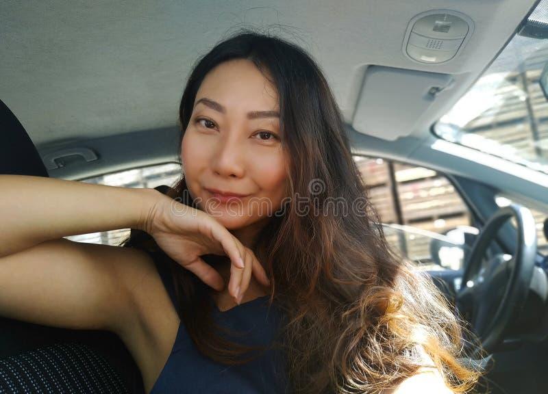 Lyckliga kvinnliga vänner som spelar och har gyckel i grönt gräs Stående av en härlig asiatisk kvinna som sitter i en bil och le arkivfoto