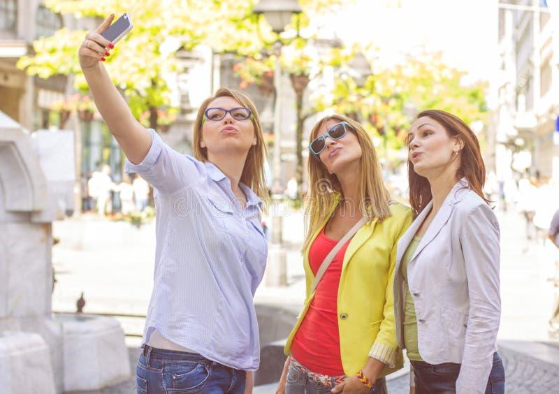 Lyckliga kvinnliga vänner som tar Selfie royaltyfria foton
