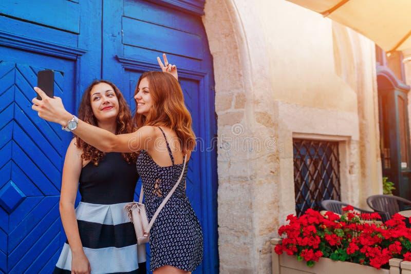 Lyckliga kvinnliga vänner som tar selfie genom att använda smartphonen som går på gamla stadsgator arkivfoto