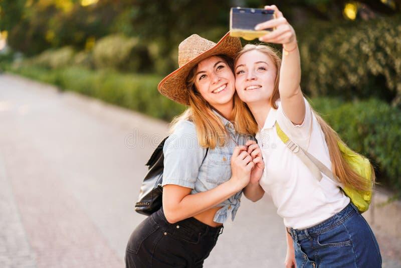 Lyckliga kvinnliga v?nner som tillsammans tar selfie arkivfoto