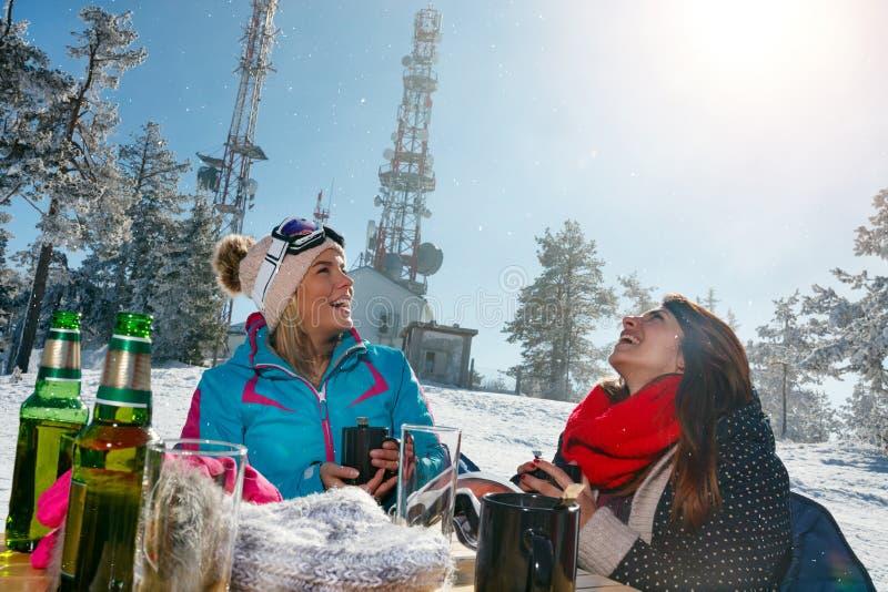 Lyckliga kvinnliga vänner som tycker om den varma drinken i kafé på, skidar semesterorten royaltyfri bild