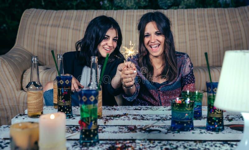 Lyckliga kvinnor kopplar ihop hållande tomtebloss i ett parti arkivfoton