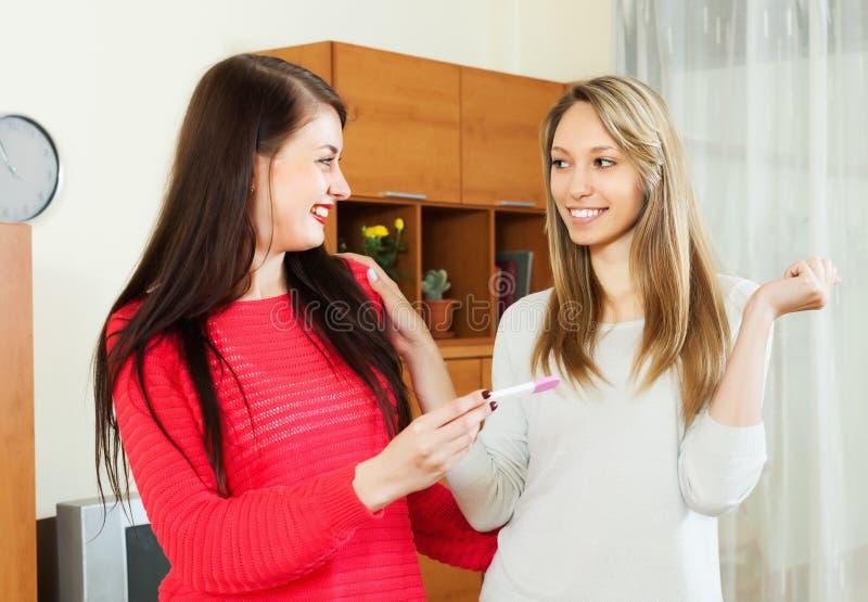 Lyckliga kvinnor med graviditetstestet royaltyfria foton