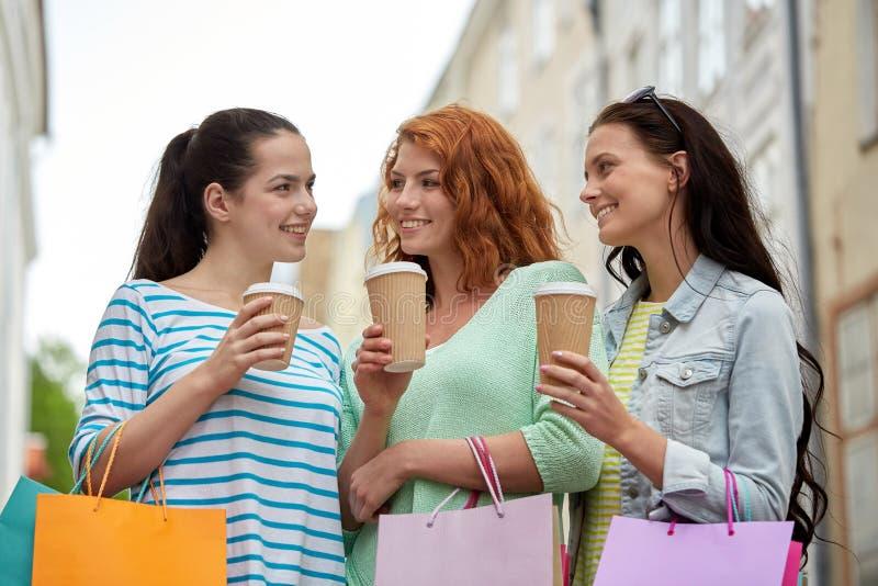 Lyckliga kvinnor med shoppingpåsar och kaffe i stad arkivfoto