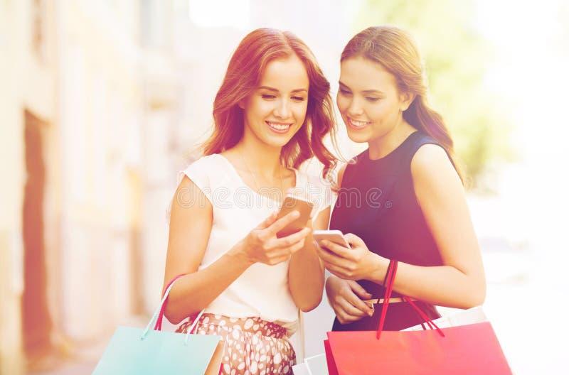 Lyckliga kvinnor med shoppingpåsar och smartphonen arkivbilder