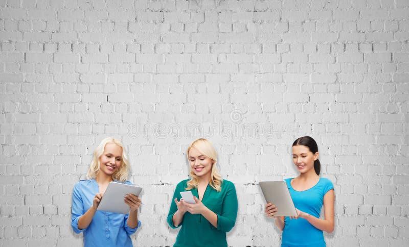 Lyckliga kvinnor med smartphone- och minnestavlaPCdatoren royaltyfri bild