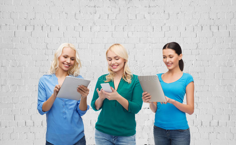 Lyckliga kvinnor med smartphone- och minnestavlaPCdatoren royaltyfri fotografi