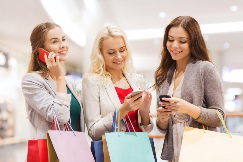 Lyckliga kvinnor med smartphones och shoppingpåsar arkivbilder