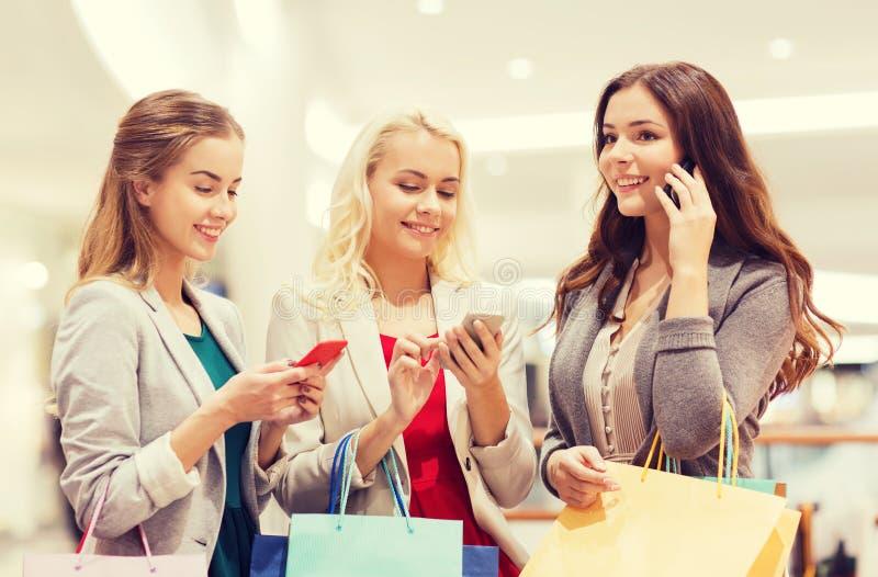 Lyckliga kvinnor med smartphones och shoppingpåsar royaltyfria bilder