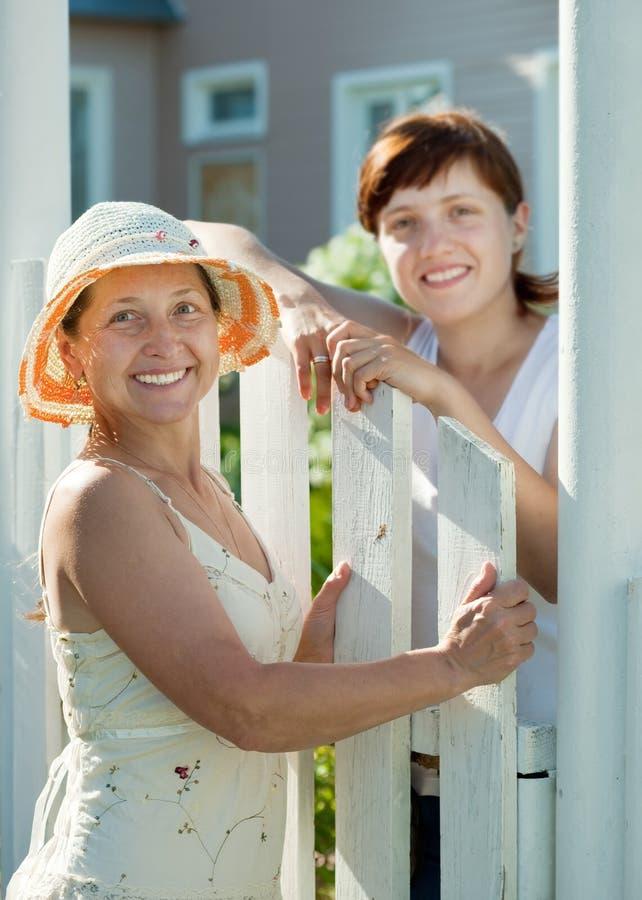 Lyckliga kvinnor nära fäktar grinden royaltyfria foton