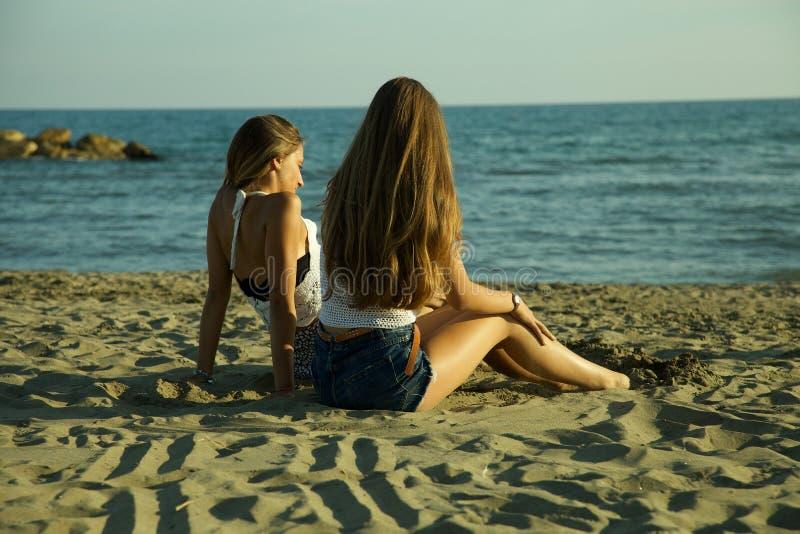 Lyckliga kvinnor på strandsammanträdet och sesolnedgången fotografering för bildbyråer