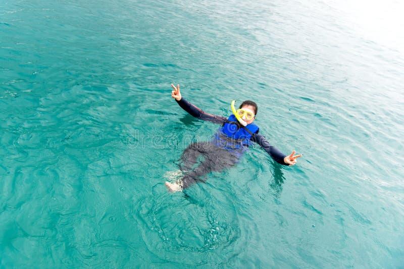 Lyckliga kvinnor poserar i blått vatten med fiskar, når de har snorklat, sommardag thailand arkivbild