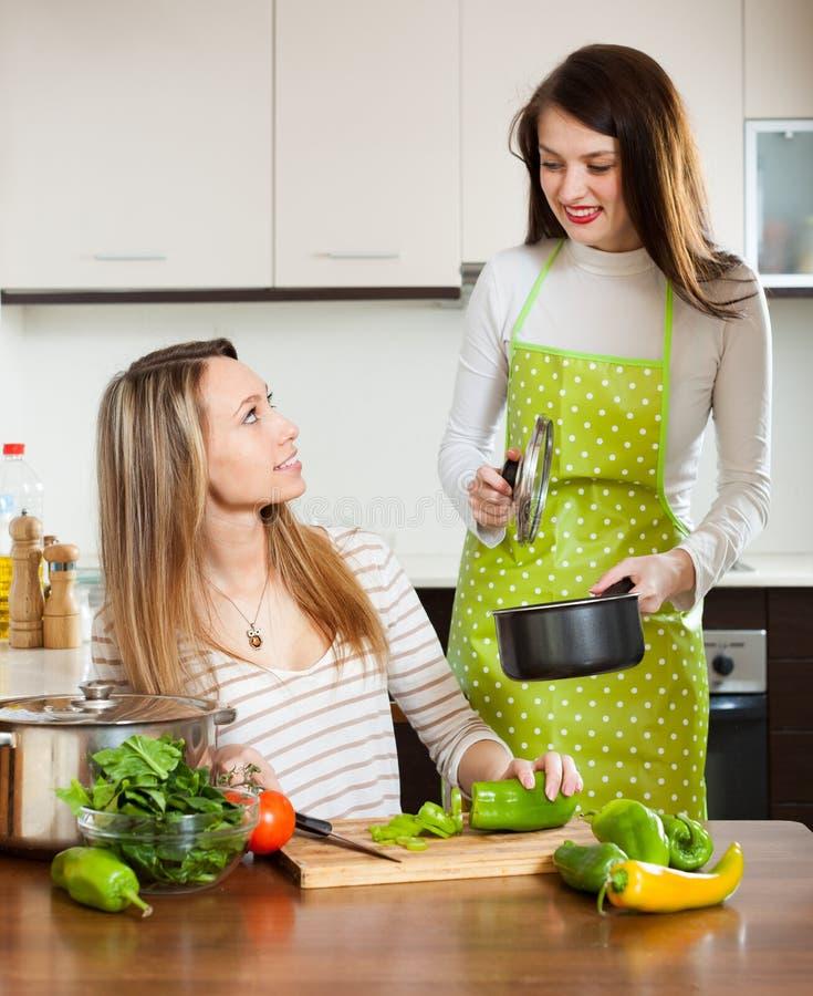 Lyckliga kvinnor som lagar mat mat fotografering för bildbyråer