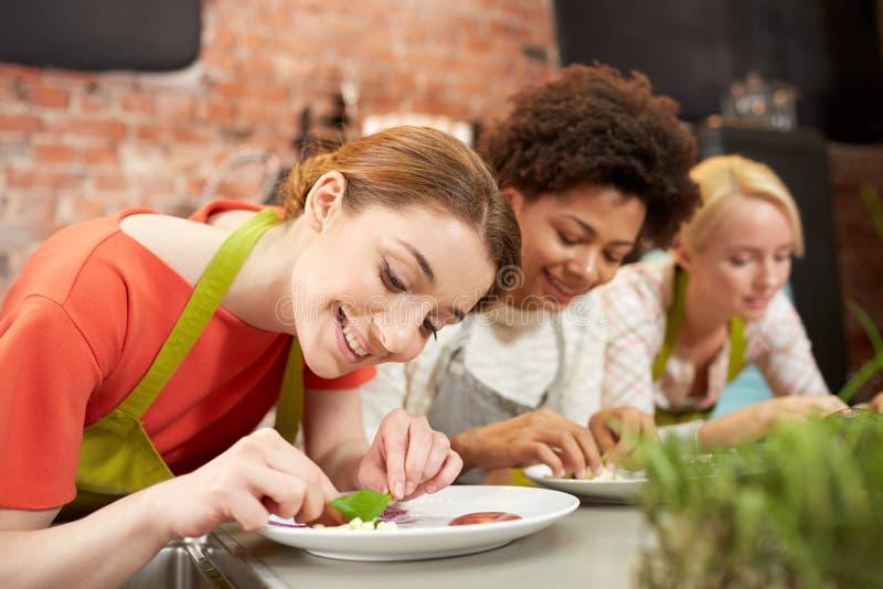 Lyckliga kvinnor som lagar mat och dekorerar disk arkivfoto