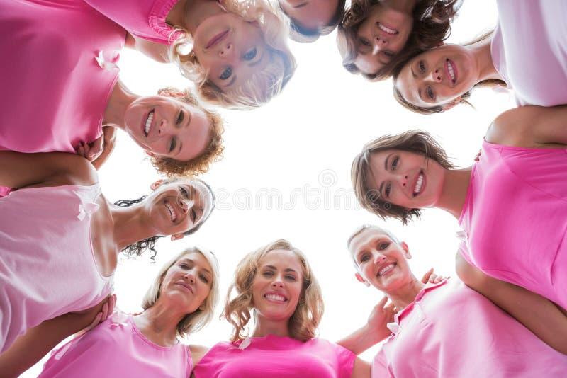 Lyckliga kvinnor som ler i bärande rosa färger för cirkel för bröstcancer royaltyfria foton