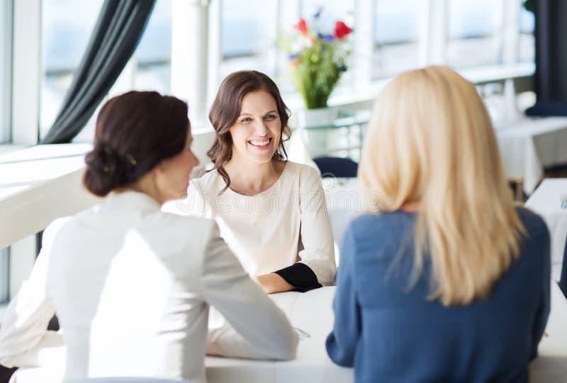 Lyckliga kvinnor som möter och talar på restaurangen royaltyfri foto