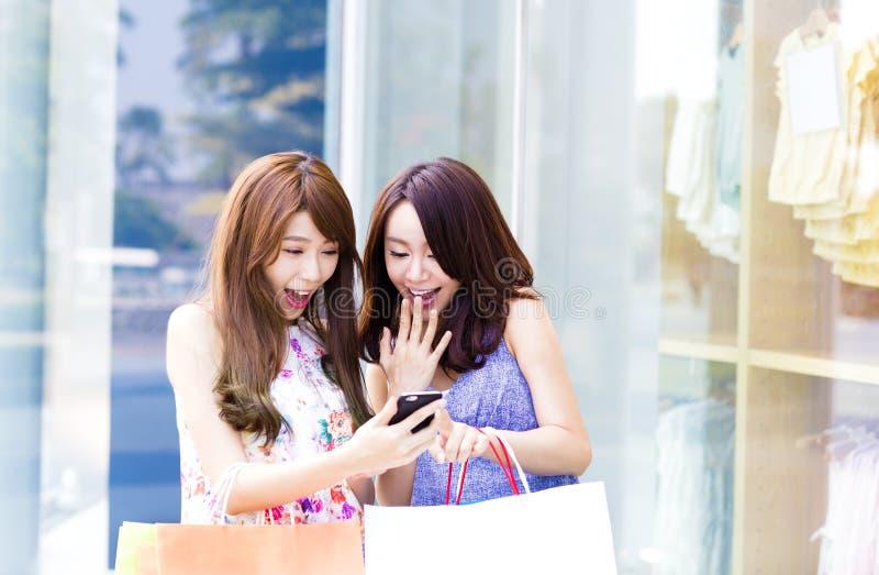 Lyckliga kvinnor som rymmer shoppingpåsar och håller ögonen på telefonen royaltyfria bilder