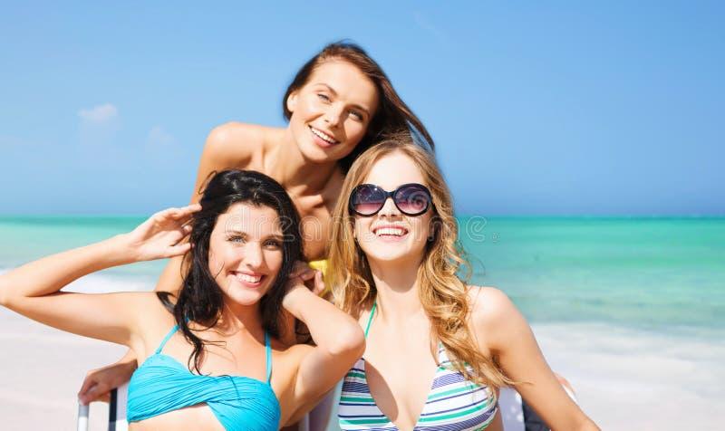 Lyckliga kvinnor som solbadar på stolar över sommarstranden royaltyfri foto