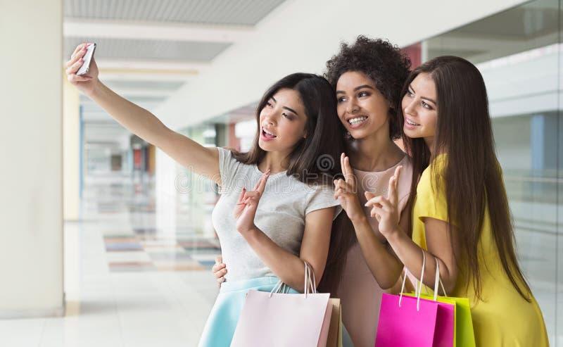 Lyckliga kvinnor som tar selfie, medan shoppa i galleria arkivfoto