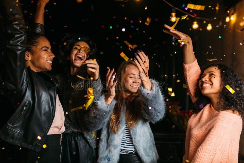 Lyckliga kvinnor som tycker om partiet på natten royaltyfri foto