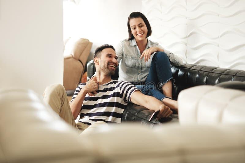 Lyckliga latinamerikanska par genom att använda Smartphones på soffan hemma royaltyfri fotografi