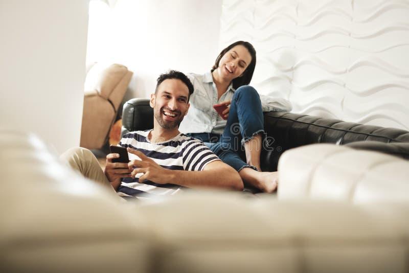 Lyckliga latinamerikanska par genom att använda Smartphones på soffan hemma arkivbild