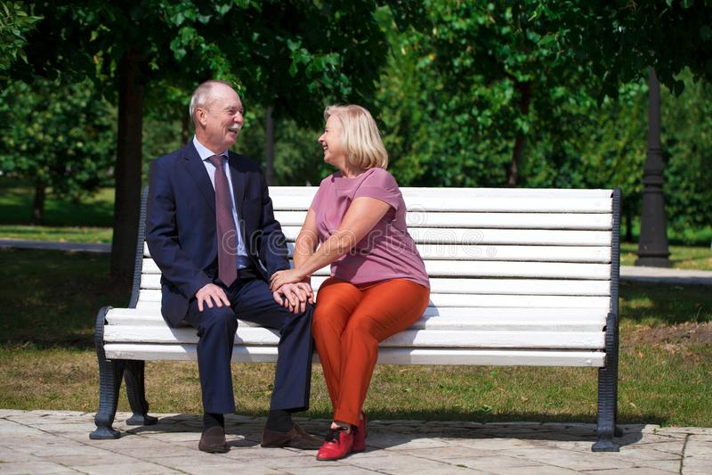 Lyckliga ?ldre par som vilar p? en b?nk royaltyfria bilder