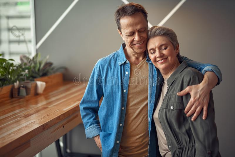 Lyckliga le åldriga par som omfamnar i kafé royaltyfri fotografi