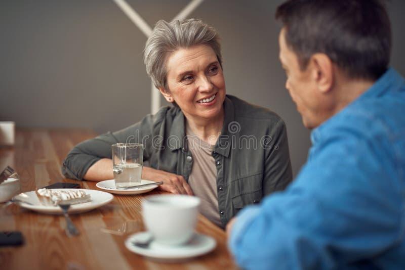 Lyckliga le åldriga par som sitter i kafé royaltyfri foto