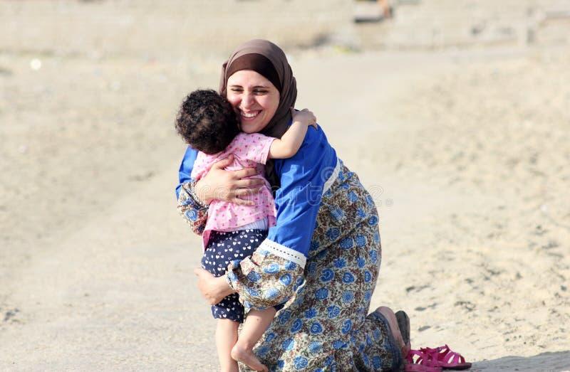 Lyckliga le arabiska muslim som modern kramar hennes, behandla som ett barn flickan arkivbilder