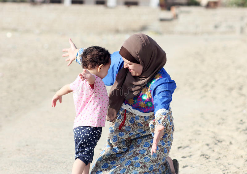 Lyckliga le arabiska muslim som modern kramar hennes, behandla som ett barn flickan royaltyfria foton