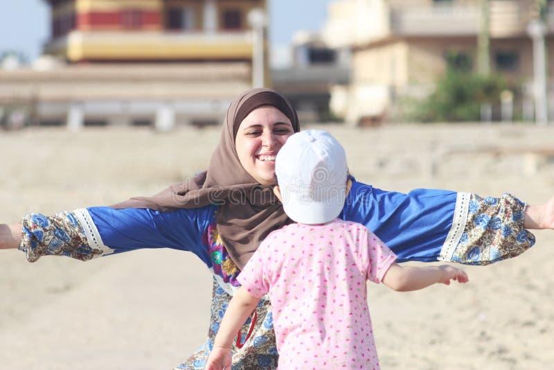 Lyckliga le arabiska muslim som modern kramar hennes, behandla som ett barn flickan arkivfoto