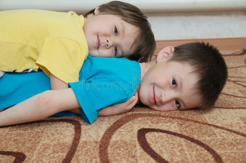Lyckliga le barn som ligger på de som trappa Syskon - pojke och liten flicka - tillsammans spela arkivbild