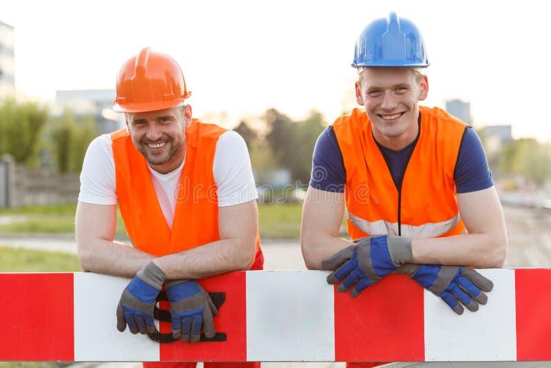 Lyckliga le byggnadsarbetare royaltyfri foto