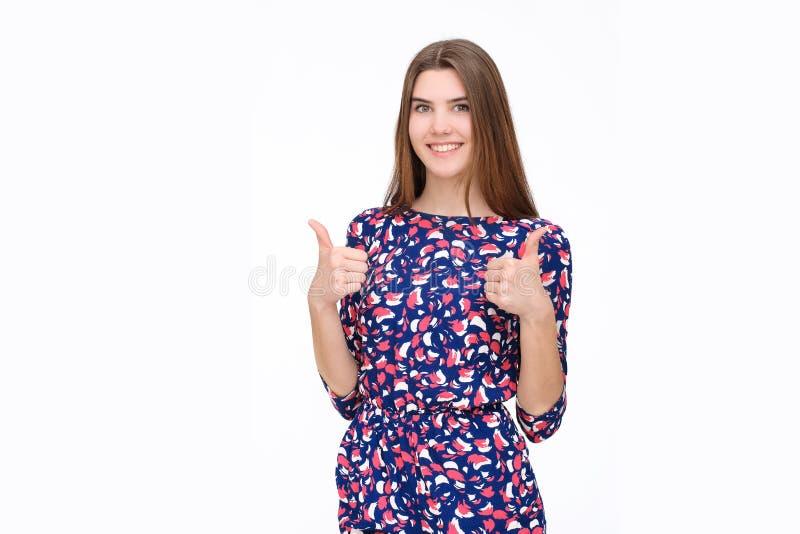 Lyckliga le härliga unga tummar för brunettkvinnavisning gör en gest upp royaltyfria foton