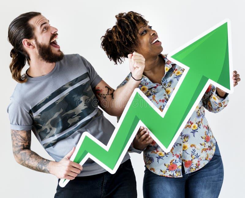 Lyckliga le mellan skilda raser par som rymmer en tillväxtpil royaltyfria foton