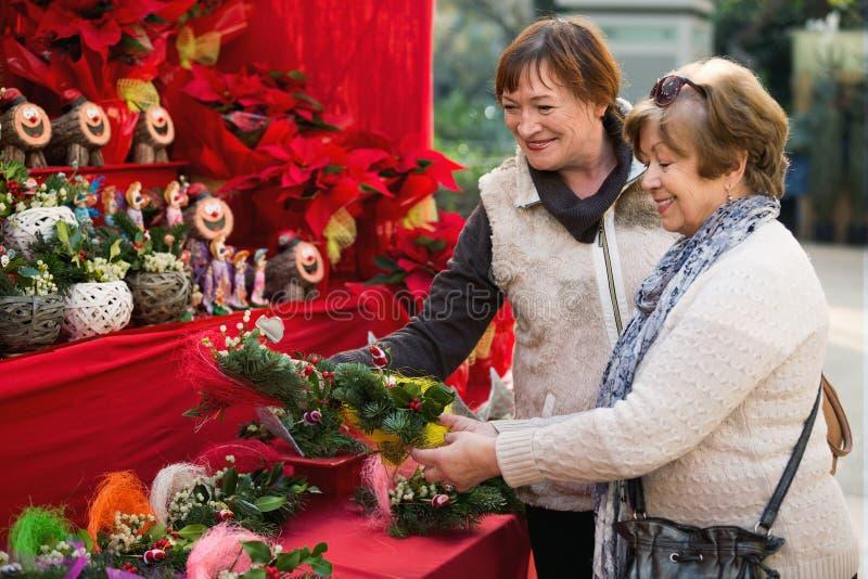 Lyckliga le mogna kvinnor som väljer blom- sammansättningar arkivbild