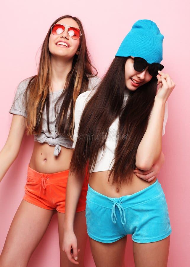 Lyckliga le nätta tonårs- flickor eller vänner som kramar över rosa färger royaltyfri foto