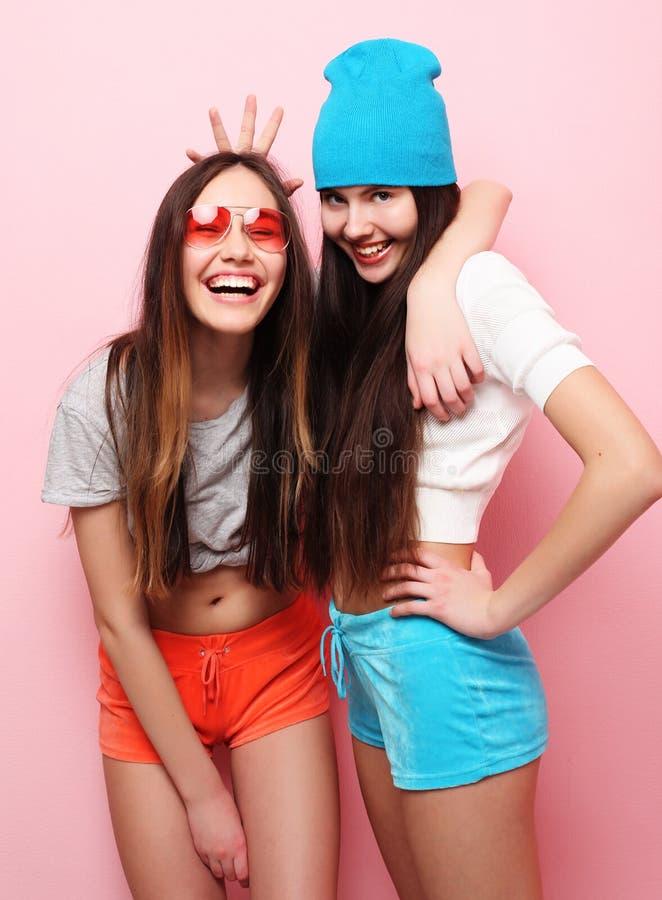 Lyckliga le nätta tonårs- flickor eller vänner som kramar över rosa färger royaltyfri fotografi